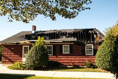 Piccola casa rossa con tetto e ultimo piano del ` s distrutti da incendio immagini stock