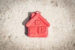 Piccola casa rossa su un fondo marrone Fotografia Stock