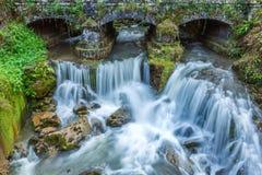 Piccola cascata al fiume della montagna sotto il vecchio ponte in Asturie, Spagna Fotografia Stock