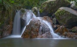 Piccola cascata con la grande pietra rossa nella foresta immagine stock libera da diritti