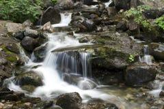 Piccola cascata della montagna fra le rocce Fotografie Stock Libere da Diritti
