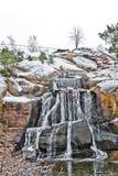 Piccola cascata nell'orario invernale a Tallinn, Estonia l'acqua scende sulle pietre nel tempo dell'inverno immagini stock