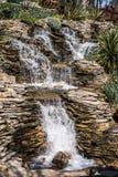 Piccola cascata rocciosa che versa in un lago immagine stock