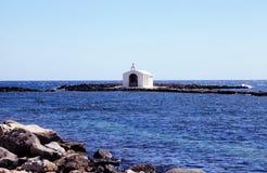 Piccola chiesa bianca in mare vicino a Georgioupolis, Creta, Grecia Immagine Stock