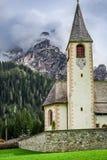 Piccola chiesa in dolomia nuvolose della montagna, Italia Immagine Stock