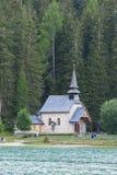 Piccola chiesa nel legno sulla riva del lago, dolomia, Italia Fotografia Stock