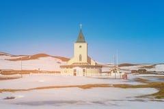 Piccola chiesa sopra la terra della neve ed alta collina con il chiaro fondo del cielo blu Immagine Stock Libera da Diritti