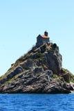 Piccola chiesa sull'isola rocciosa alta Fotografia Stock