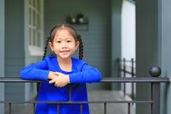 Piccola condizione asiatica felice della ragazza del bambino alle barre del balcone della casa ed alla macchina fotografica osser fotografia stock libera da diritti