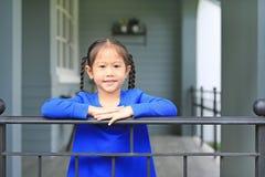 Piccola condizione asiatica felice della ragazza del bambino alle barre del balcone della casa ed alla macchina fotografica osser immagine stock libera da diritti