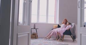 Piccola condizione della figlia della madre allegra nel salone a casa che muove ballare verso la canzone favorita insieme Il bamb archivi video