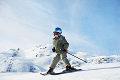 Piccola corsa con gli sci del bambino sul pendio della neve Fotografie Stock Libere da Diritti