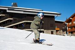 Piccola corsa con gli sci del bambino sul pendio della neve Immagini Stock Libere da Diritti
