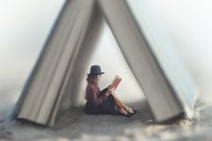 Piccola donna che legge una legge del libro protettiva da una casa fatta da un libro gigante immagine stock