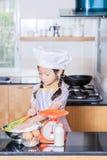 Piccola farina di frumento asiatica di scalpore della ragazza che produce pancake Immagini Stock