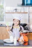 Piccola farina di frumento asiatica di scalpore della ragazza che produce pancake Fotografia Stock