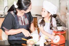 Piccola farina di frumento asiatica di scalpore della ragazza che produce pancake Fotografie Stock