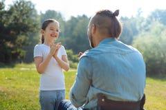 Piccola figlia che gioca picchiettio-un-dolce con suo padre disabile Immagini Stock Libere da Diritti