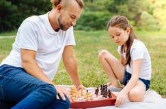 Piccola figlia che gioca scacchi con suo padre all'aperto Fotografia Stock Libera da Diritti