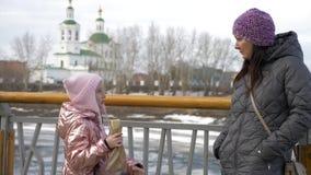 Piccola figlia che mangia hot dog squisito e che parla con la madre nell'inverno video d archivio