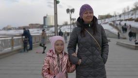 Piccola figlia che parla, tenentesi per mano con la madre e camminante sulla banchina archivi video