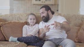 Piccola figlia sveglia con il suo film interessante di sorveglianza del padre divertente sulla TV con le grandi emozioni in salon stock footage