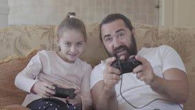 Piccola figlia sveglia con suo padre divertente che gioca i video giochi sulla TV con le grandi emozioni in salone accogliente Pa archivi video