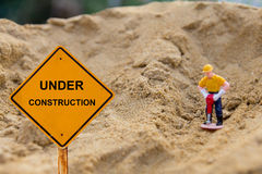 Piccola figura di una terra di scavatura dell'uomo con il messaggio in costruzione Fotografia Stock