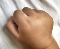 Piccola fine del pugno su del ragazzo infantile sul panno bianco immagini stock libere da diritti