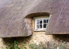 Piccola finestra di legno sotto il tetto ricoperto di paglia Fotografia Stock Libera da Diritti