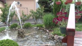 Piccola fontana nel cortile, fiori decorativi nella parte posteriore archivi video