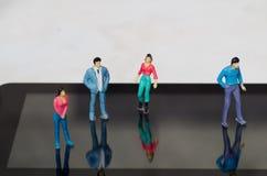 Piccola gente miniatura, amici all'aria aperta sopra uno schermo di una compressa, in un fondo bianco Immagini Stock Libere da Diritti