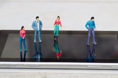 Piccola gente miniatura, amici all'aria aperta sopra uno schermo di una compressa, in un fondo bianco Immagini Stock