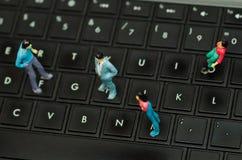 Piccola gente miniatura, gruppo di amici sopra una tastiera di computer, in una visualizzazione superiore vaga del fondo Fotografia Stock