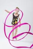 Piccola ginnasta ritmica femminile caucasica in vestito competitivo professionale che fa le spirali artistiche del nastro Immagini Stock Libere da Diritti