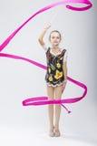 Piccola ginnasta ritmica femminile caucasica in vestito competitivo professionale che fa le spirali artistiche del nastro Immagine Stock Libera da Diritti