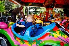 Piccola guida adorabile della ragazza del bambino sull'automobile divertente sul carosello della rotonda in parco di divertimenti fotografie stock