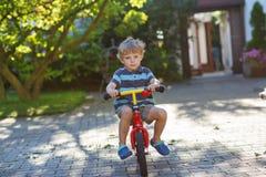 Piccola guida del ragazzo del bambino sulla sua bicicletta di estate. Immagini Stock Libere da Diritti