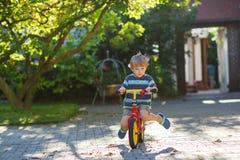 Piccola guida del ragazzo del bambino sulla sua bicicletta di estate. Fotografie Stock