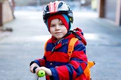 Piccola guida prescolare sveglia del ragazzo del bambino sul motorino che guida alla scuola Fotografia Stock