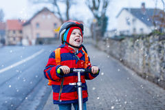 Piccola guida prescolare sveglia del ragazzo del bambino sul motorino che guida alla scuola Fotografie Stock