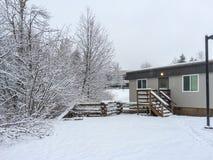 Piccola iarda coperta di neve davanti alla casa il giorno di inverno nel Canada immagini stock