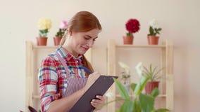 Piccola impresa Apertura del negozio di fiore Una ragazza in una camicia di plaid ed in un grembiule a strisce che tengono un seg archivi video