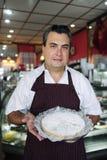 Piccola impresa: cameriere che mostra una torta saporita Fotografie Stock Libere da Diritti
