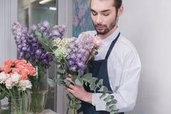 Piccola impresa Fiorista maschio nel negozio di fiore Studio di progettazione floreale, prendendo le decorazioni ed accordi fotografia stock libera da diritti