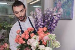 Piccola impresa Fiorista maschio nel negozio di fiore Studio di progettazione floreale, prendendo le decorazioni ed accordi fotografie stock