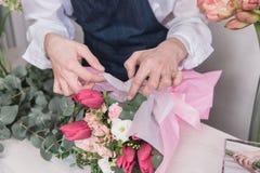 Piccola impresa Fiorista maschio nel negozio di fiore Studio di progettazione floreale, prendendo le decorazioni ed accordi fotografie stock libere da diritti