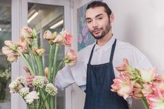 Piccola impresa Fiorista maschio nel negozio di fiore Studio di progettazione floreale, prendendo le decorazioni ed accordi fotografia stock