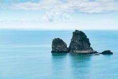 Piccola isola della roccia sull'orizzonte del litorale fotografia stock