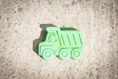 Piccola macchina di verde su un fondo marrone Fotografia Stock